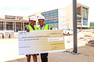Ms Zama Luthuli (R) hands over a R10m cheque to Ms Sibongile Mkhabela, CEO of the NMCHT.