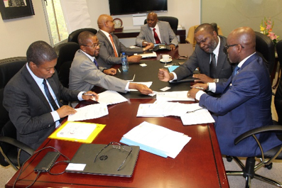 CEO Mr Geoffrey Mvuleni Qhena, center left, signing on behalf of IDC